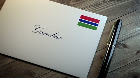 Country name written on a card or envelope in cursive font with a sleek pen on a wooden table surface under beautiful classy light. Stamp in the corner shows the flag of Gambia