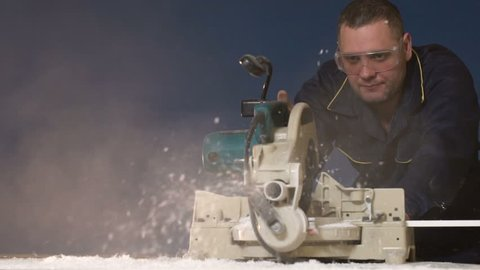 Worker in overalls on blue background cuts out a slow motion wood item on the electric saw. A stream of sawdust from the machine tool when processing a tree. The shavings fly to the camera with smoke.