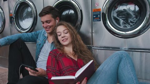Beautiful couple in a laundry listen to the music on the phone, reading book, watching videos. Handsome young man with stylish haircut in jeans shirt. Woman with curly red hair in tartan shirt.