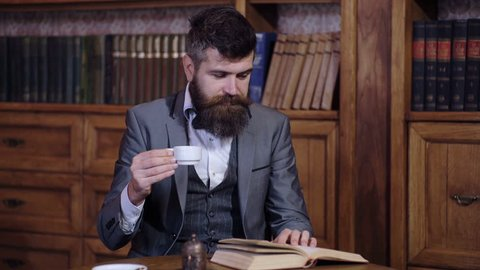 An intelligent bearded man reads a book. A respectable man drinks morning coffee and reads a book in the library