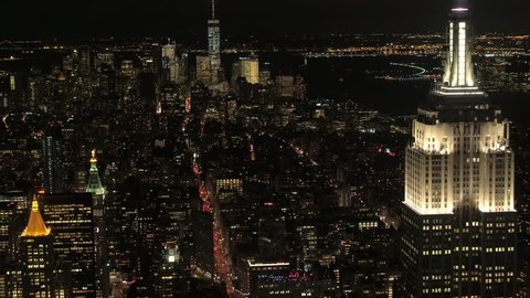 AERIAL HELI SHOT, CLOSE UP: Flying past iconic lit up with lights Empire State Building towards Lower Manhattan financial district. Traffic lights on busy crowded with cars 5th avenue at night in NYC