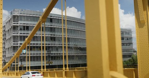 A daytime tracking dolly shot of a modern Pittsburgh office building as seen through the yellow steel beams of the Andy Warhol Bridge.