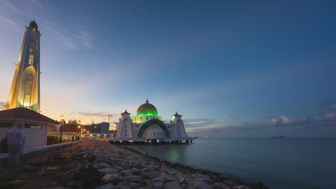Dramatic Time lapse of sunrise and scattered clouds at Malacca Straits Mosque in Melaka, Malaysia at night to day. Motion timelapse pan down. Full HD 1080p.
