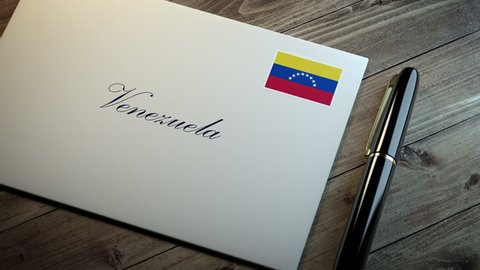 Country name written on a card or envelope in cursive font with a sleek pen on a wooden table surface under beautiful classy light. Stamp in the corner shows the flag of Venezuela