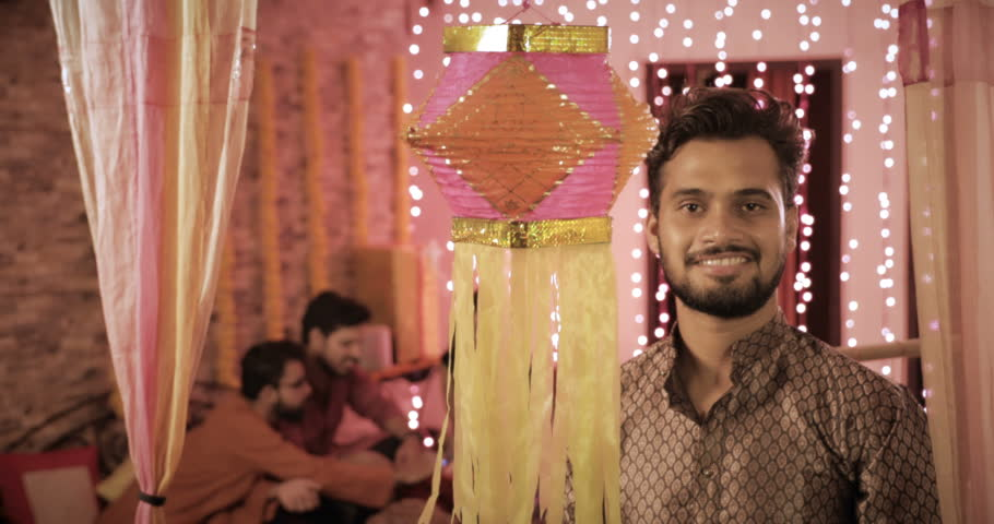 A smiling handsome man hanging a Diwali traditional lantern during the festival. A young happy male wearing kurta hanging colorful Diwali Kandil while his colleagues sitting in the background
