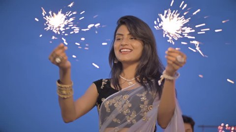 A Young and beautiful woman in a traditional sari playing with fire sparkle or firecracker. Slow motion shot of an attractive and smiling lady playing with fireworks outdoors during Diwali Festival