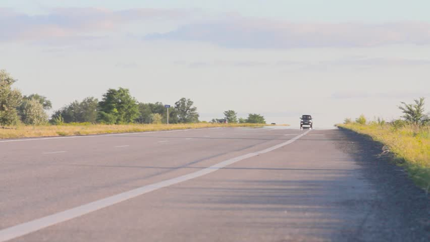 The car is driving along the highway. Asphalt road between agricultural fields and driving cars. Shallow depth of field. Front view. | Shutterstock HD Video #1015233313