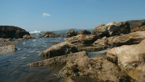 Blue waves washing rocks gently, blue clear sky and calm relaxing atmosphere at the seaside on boiling summer day