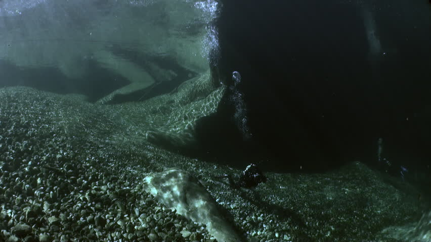Camera operator in refraction of sunlight underwater in transparent river. Shooting a frame of picturesque nature on background of huge smooth stones in Verzasca. | Shutterstock HD Video #1015244173