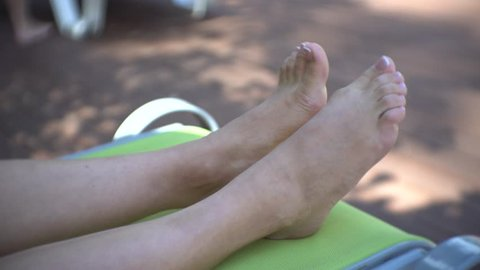 Female feet on sunbed by swimming pool