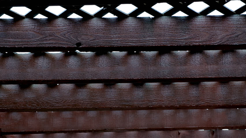 Rain dripping from wooden trellis during storm. | Shutterstock HD Video #1015264153