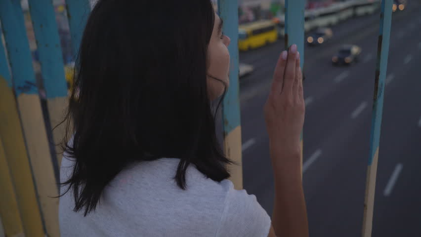 Cute Depressive Brunette Hitch Walking On A Bridge. A woman walks along the side of the highway and looks thoughtfully at the cars. Warm summer evening. average size of the frame. Probes of teenagers. | Shutterstock HD Video #1015265323