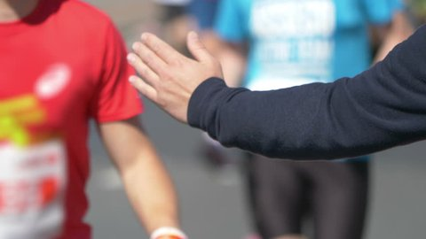 Man giving runners high five in 4k slow motion 60fps