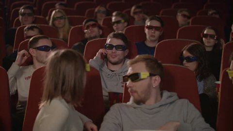 Man talking on phone in cinema hall. Uncultured man disturb people in movie theatre. Man bothering people watching 3d film in cinema. Uncultured manners at cinema
