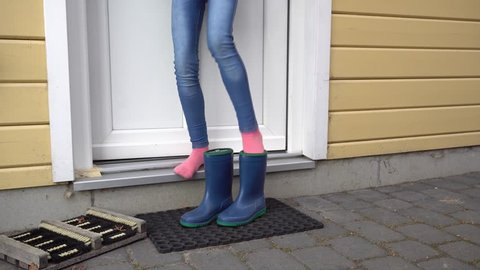 Child comes out of the house and gets into blue rubber boots and walk away