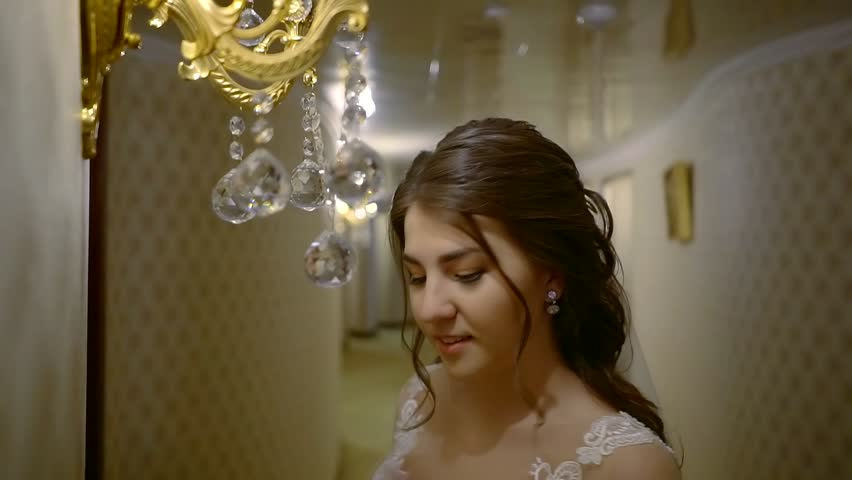 pretty Tatar bride in a wedding dress stands in the hotel corridor next to the lamp and corrects the earring in her ear