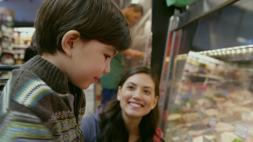 Handheld shot of happy mother talking to son looking at display cabinet in supermarket