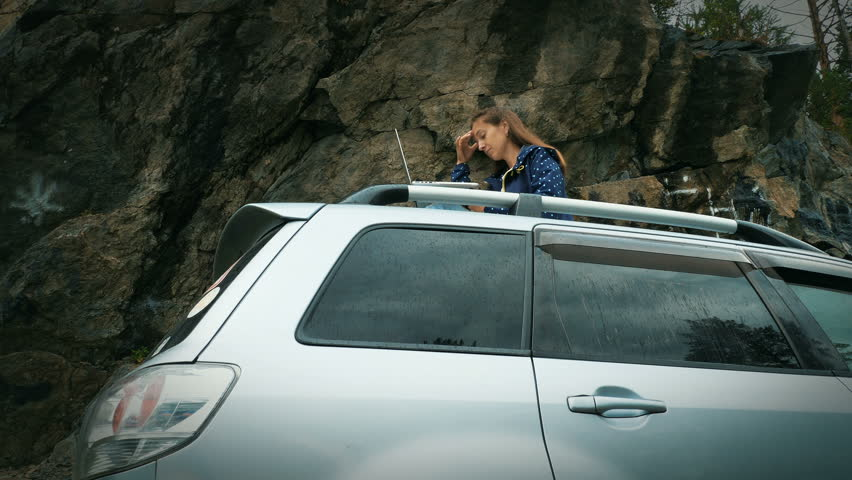 Side view of female freelancer work remotely on laptop, while sit on the roof of her car against rocks. Rocky mountain at the background. #1015295923