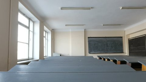 Desks in empty classroom, lecture hall in the College, School, University. The study hall represents lack of state funding