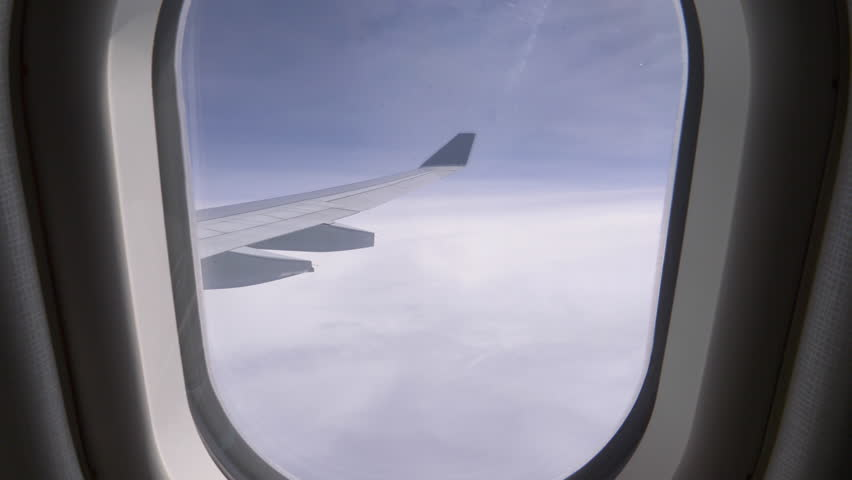 POV, CLOSE UP: Unknown person pulls up airplane window shade and reveals a stunning view of the bright blue sky. Looking through small window at wing of commercial airplane cruising at high altitude.