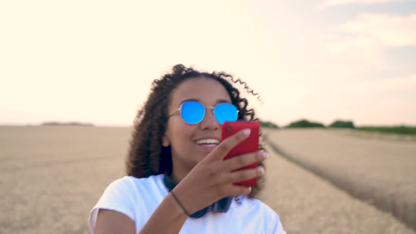 Slow motion follow shot video of beautiful mixed race African American girl teenager young woman in white T-shirt and blue sunglasses walking using her smart cell phone