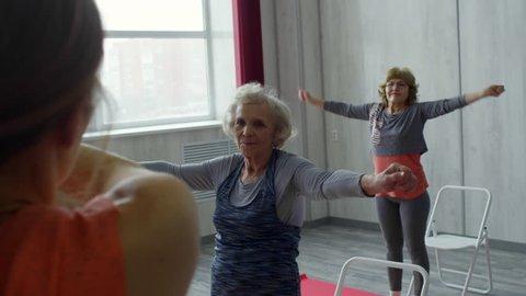 Over the shoulder shot of fit female fitness trainer and group of senior people in sportswear warming up stiff muscles: they are doing arm circles exercise
