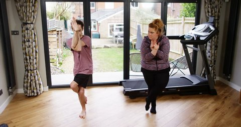 4K Funny fitness concept, unfit obese woman trying & failing to get into yoga pose. Slow motion.