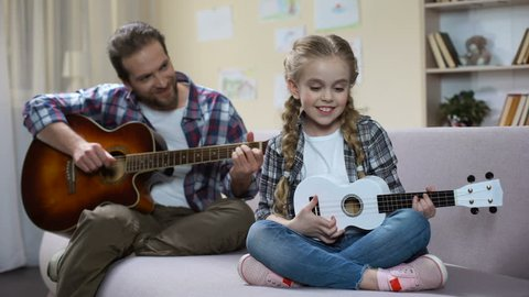 Dad with guitar and daughter with ukulele playing song, competition rehearsal