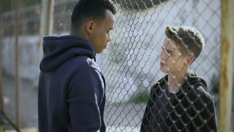Two boys of different nationalities talking, rich and poor separated by fence