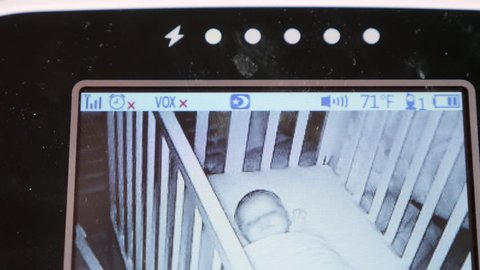 A shot of a baby monitor with a cute newborn baby girl sleeping in her crib