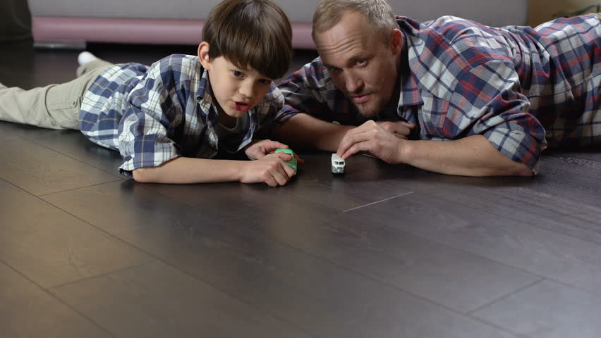 Daddy and his child competing in launching of small toy cars, happy childhood