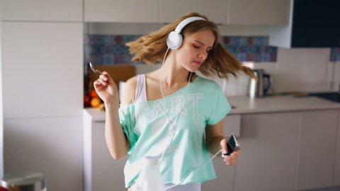 Sexy girl dancing at home. Dancing woman eating cornflakes breakfast in kitchen. Expressive girl having fun in morning. Dancing girl listening music in headphones. Enjoying new day