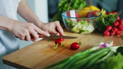 Woman hands with knife cutting radishes for salad. Close up fresh vegetables on kitchen table. Housewife cooking natural and healthy meal on wooden board. Seasonal vegetables ingredients for salad