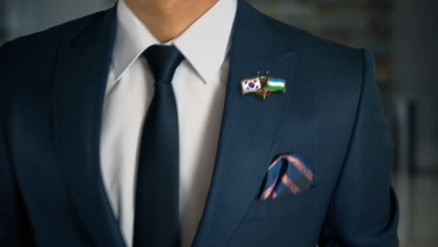 Businessman Walking Towards Camera With Friend Country Flags Pin South Korea - Uzbekistan