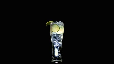 Wide shot tall glass of soda water with lime slices and wedges and ice cubes inside, fizzy bubbles rising. Rotating in slow motion.