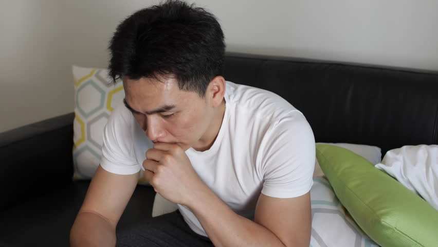 An Asian man chatting with his friend on the phone, texting and life chat to camera.He has a smiling face and sad face with sitting and lying on the sofa | Shutterstock HD Video #1015462573