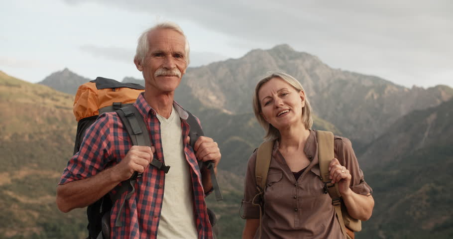 Positive old caucasian couple trekking in mountains with backpacks, enjoying their adventure - portrait shot 4k #1015494793