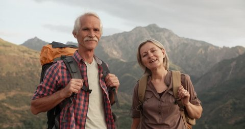 Positive old caucasian couple trekking in mountains with backpacks, enjoying their adventure - portrait shot 4k