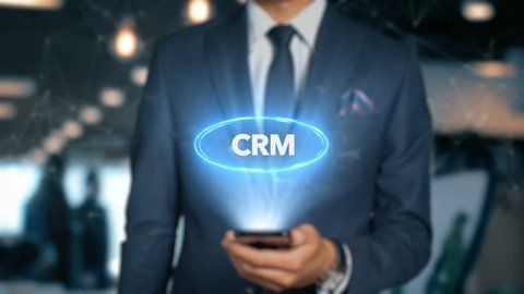 Businessman With Mobile Phone Opens Hologram HUD Interface and Touches Word - CRM