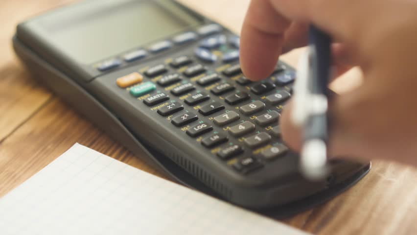 A close up of a hand with pencil using a scientific calculator.