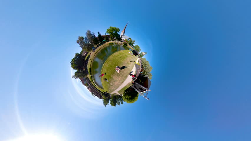 A panoramic little planet scene of the people in the park playing with the zorb ball with the trees on the side