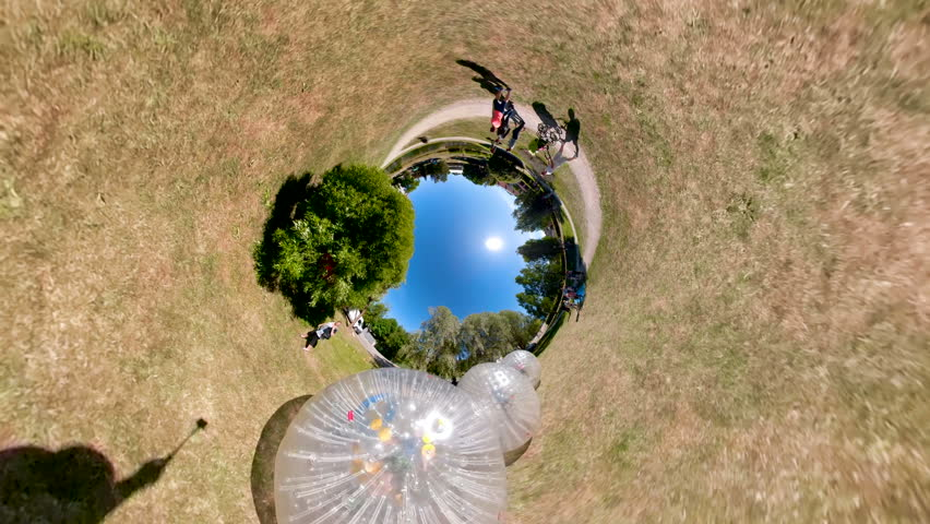 The panoramic little planet view of the three zorb balls in an open park on a sunny day