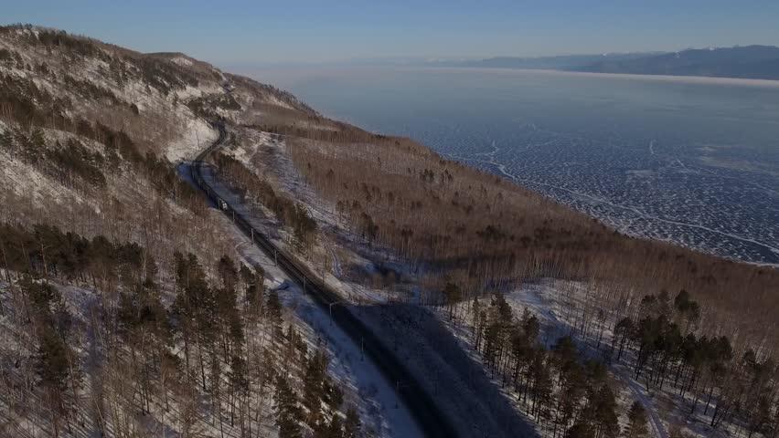 Winter day Aerial drone follow Trans-Siberian railway passengers tourist train near Baikal lake ice. Cinematic professional 4k footage. Cold snow Siberia Russia best journey. High altitude
