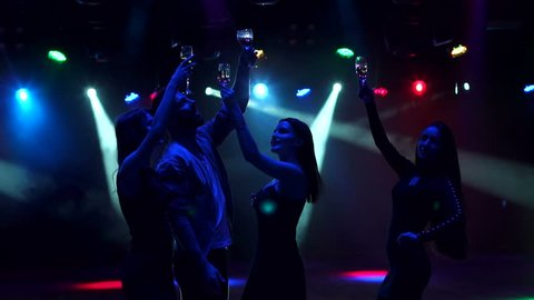 Silhouette of happy teenagers dancing at the party, slow motion. A group of young people are dancing in a nightclub, they are holding champagne and raising their hands up.