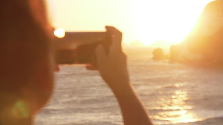 Young woman taking pictures with smartphone of the sea at sunset on island coast 17_Ponza_GH5_13 | Shutterstock HD Video #1015568143