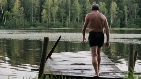 Caucasian mature man jumping from wooden pier in lake. Having fun in vacation in country side.