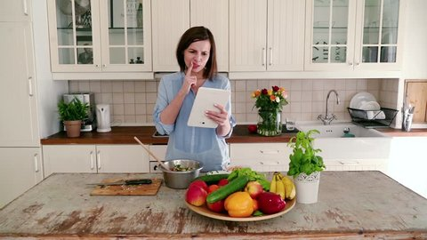 Woman checking recipe on tablet during making salad and finding she forgetting one ingredient
