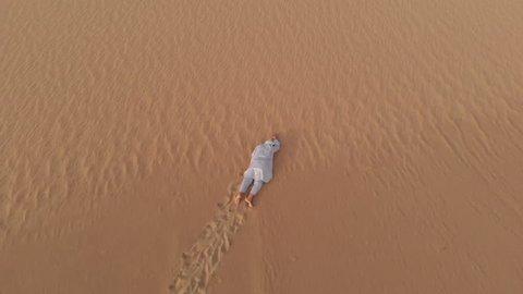 Tuareg man crawling in a desert