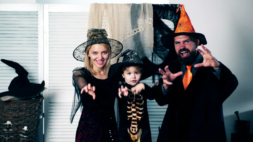 Happy family mother father and son in costumes on a celebration of Halloween. Halloween celebration concept. Dad with mom and their son in hats and skeleton suit scare to halloween