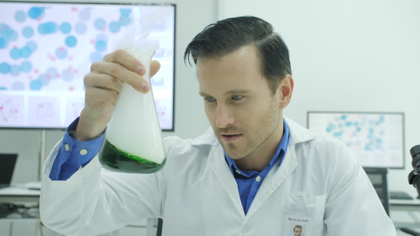 Portrait of Crazy and mad scientist laughing and holding volumetric flask with green liquid in laboratory.